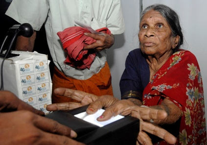 A villager uses a fingerprint scanner during the Unique Identification (UID) process in Patancheru