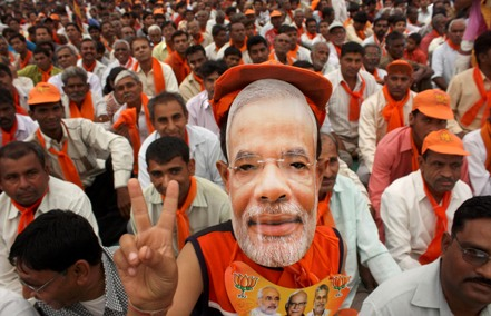 A BJP supporter wears a mask of Gujarat's Chief Minister Modi at a rally in Balasinor