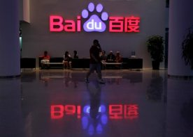 """A employee uses his mobile phone as he walks past the company logo of Baidu at its headquarters in Beijing, August 5, 2010. REUTERS/Barry Huang/File Photo     GLOBAL BUSINESS WEEK AHEAD PACKAGE - SEARCH """"BUSINESS WEEK AHEAD JULY 25"""" FOR ALL IMAGES - RTSJGAV"""