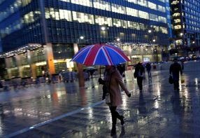 Workers walk in the rain at the Canary Wharf business district in London, Britain November 11, 2013. REUTERS/Eddie Keogh/File Photo - RTX2IESC