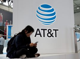 A woman looks at her mobile next to AT&T logo during the Mobile World Congress in Barcelona, Spain February 25, 2016.