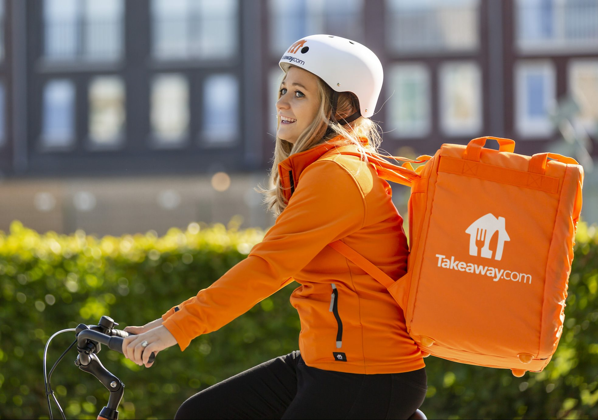 A girl on the bike is delivering food for Takeaway.com